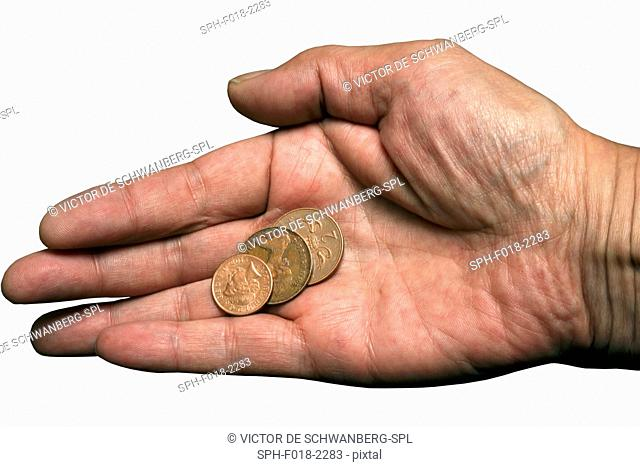 Coins on palm of hand, studio shot
