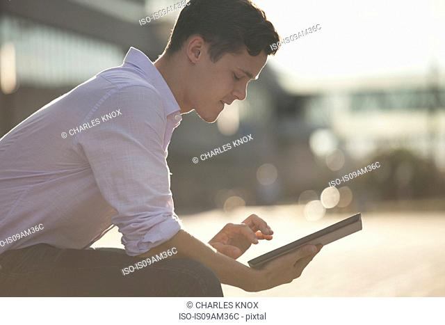 Young male higher education student sitting on bench using touchscreen on digital tablet