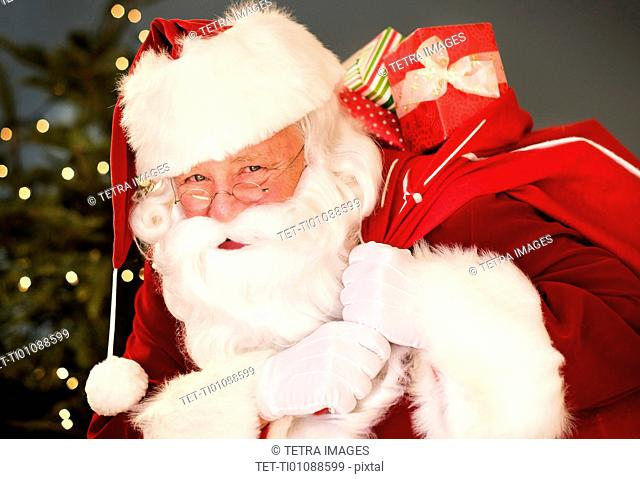 Portrait of Santa Claus carrying sack over shoulder