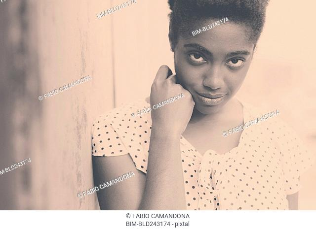 Smiling African American woman leaning on wall