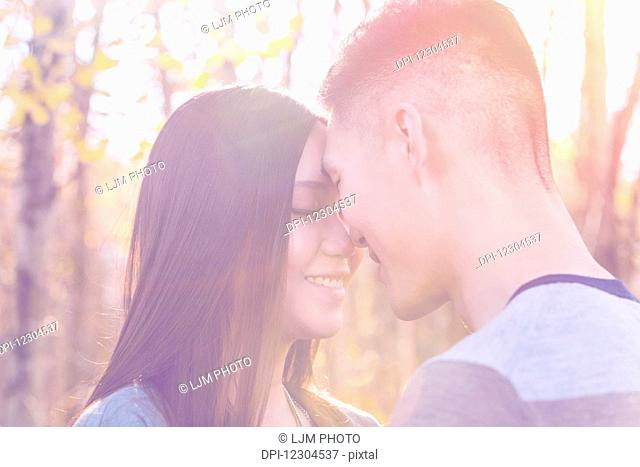 A young Asian couple enjoying quality time together outdoors in a park in autumn and touching their foreheads together affectionately in the warmth of the...