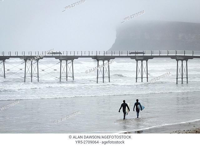 Surfers near Saltburn`s Victorian pier as sea fog roll in of the North sea at Saltburn by the Sea, North Yorkshire, England, United Kingdom