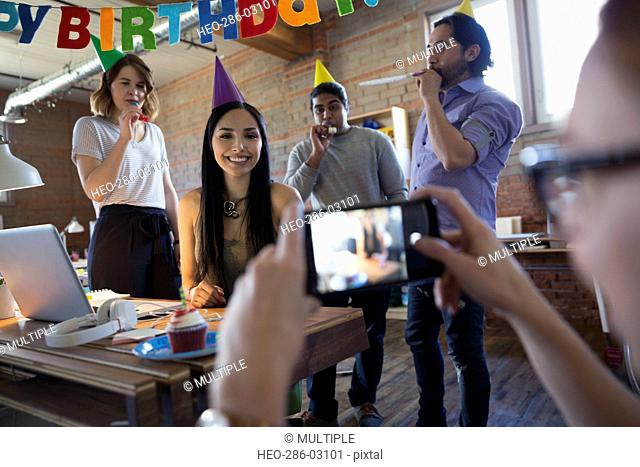 Coworker photographing businesswoman enjoying birthday party in office