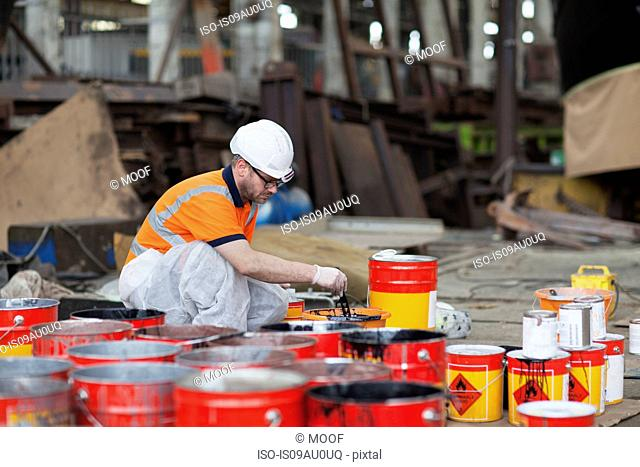 Worker mixing paints in shipyard
