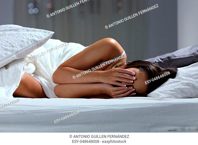 Sad woman lying on a bed at home in the night