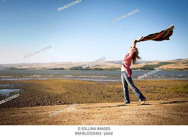 Caucasian woman holding blanket in wind