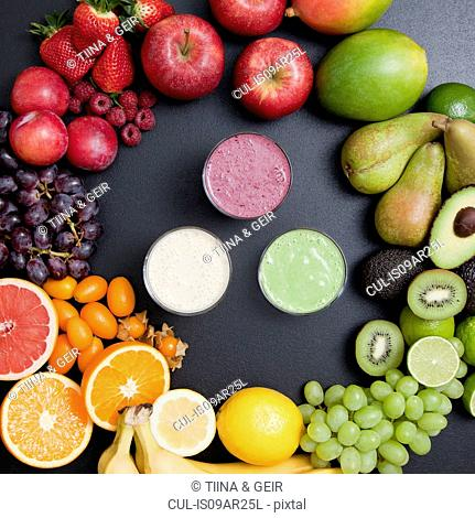 Overhead still life of variety of fruit surrounding fresh smoothies