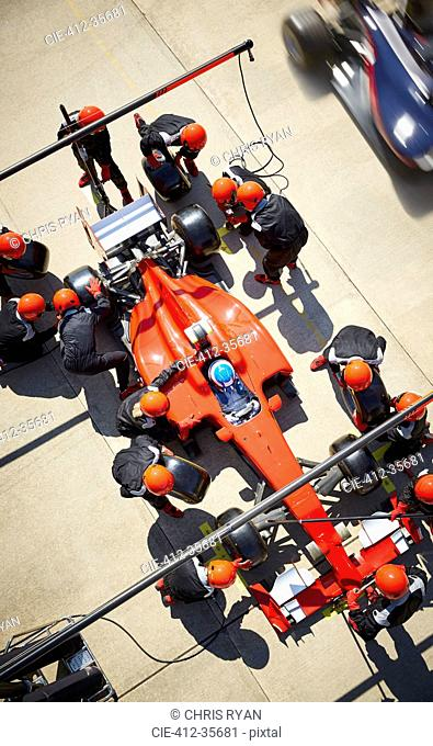 Overhead pit crew working on formula one race car in pit lane