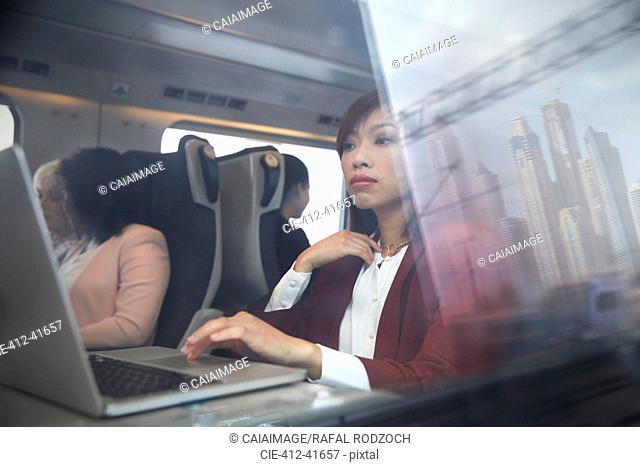 Focused businesswoman working at laptop on passenger train