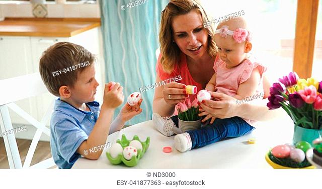 Mother and children painting colorful eggs. Mom, toddler and preschooler paint and decorate Easter egg