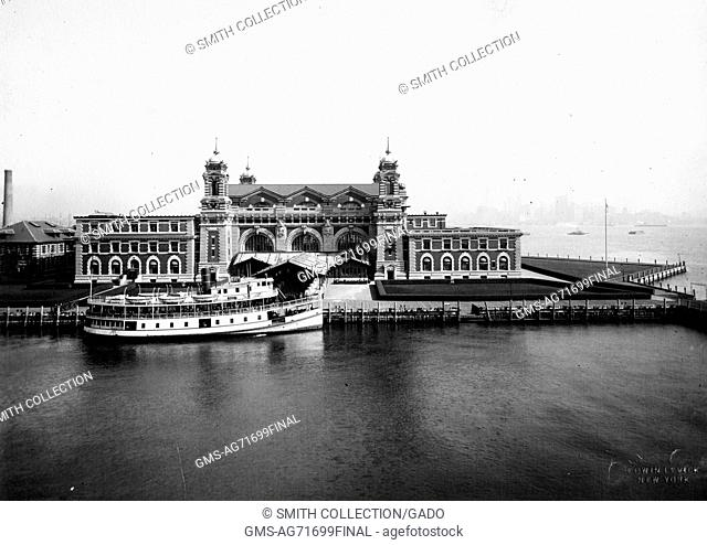 An exterior photograph of the front facade of the Ellis Island immigration inspection station, the French Renaissance Revival building is constructed with red...