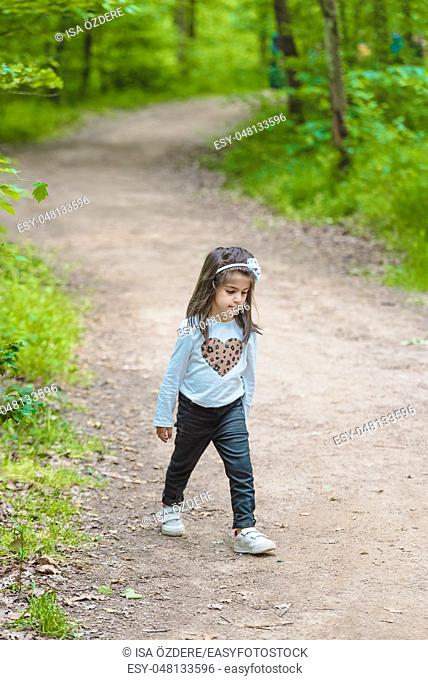 Adorable four years old cute little girl walks on a rural road in near a pod or lake at park in a sunny day