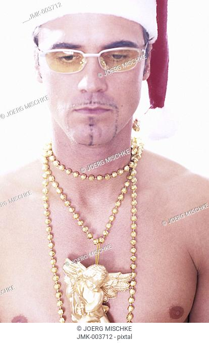 A young man, 20-25 25-30 30-35 years old, stripped to the waist, wearing a Santa Claus cap, a golden necklace and sunglasses