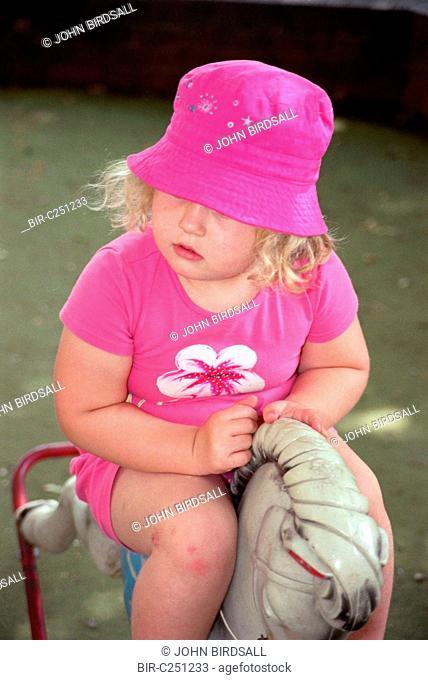 Nursery school girl playing on rocking horse