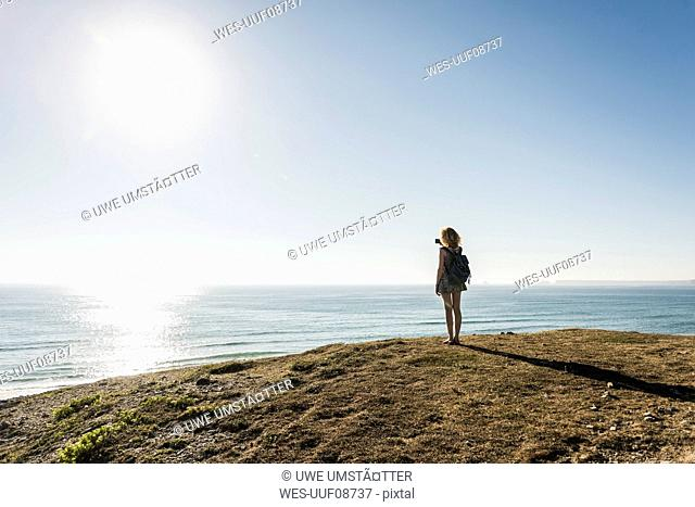 Back view of teenage girl taking picture with smartphone at seaside in the evening twilight