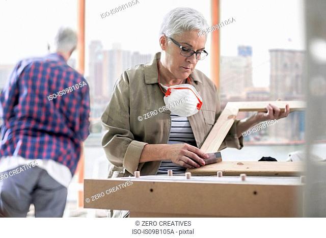 Mature female carpenter sanding picture frame in furniture making workshop