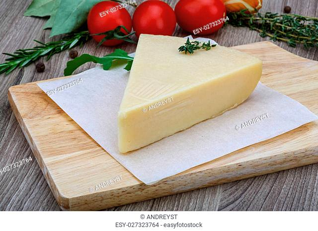 Italian Parmesan cheese with herbs on the wood background
