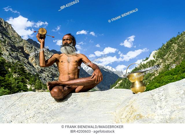 Mahant Naomi Giri, a 52 years old Sadhu, is sitting in lotus pose, padmasana, on a rock at the banks of the holy river Ganges, using his drum and praying