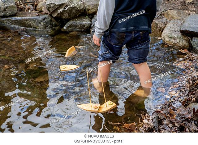 Child Playing with Toy Boats in Pond