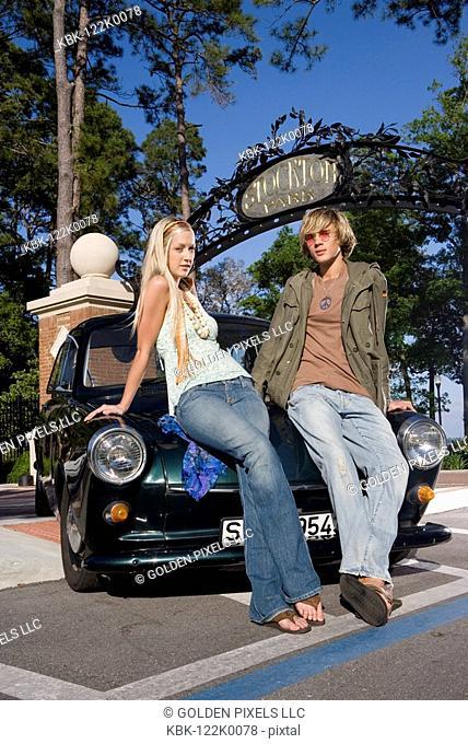 Hippie couple sitting on car hood