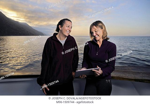 Pair of female divers looking at tablet after a day of diving, San Clemente Island, California, USA