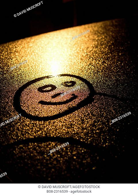 smiley face drawn in condensation on a car roof, Britain