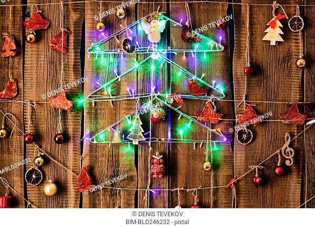 Christmas ornaments hanging on string on wood
