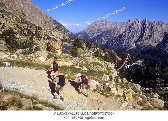 Hikers climb to the Amitges refuge, in background at right Encantats mountains, Aigüestortes i Estany de Sant Maurici National Park,Pyrenees, Lleida province