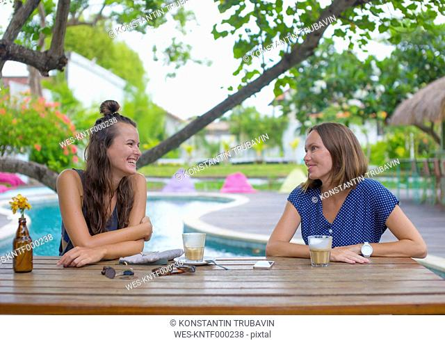 Two happy woman sitting at table at the poolside talking