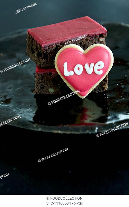 Brownies with red icing and a heart-shaped biscuit
