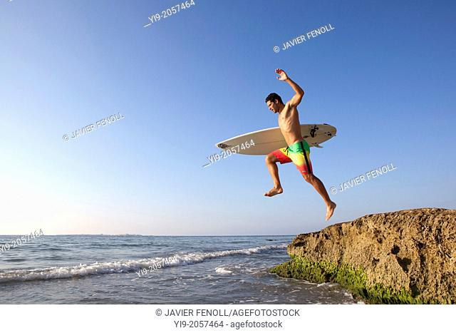 Man jumping into the water with his surf board