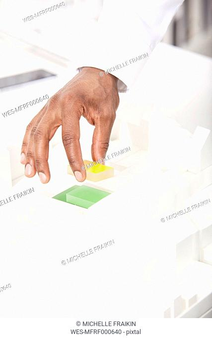 Man's hand putting building block on architectural model, close-up