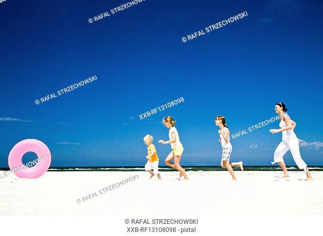 kids running after ball on beach