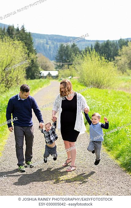 Lifestyle portrait of a family of four people outdoors in a natural field in Oregon