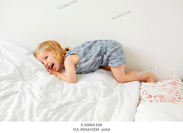 Cute female toddler playing on bed