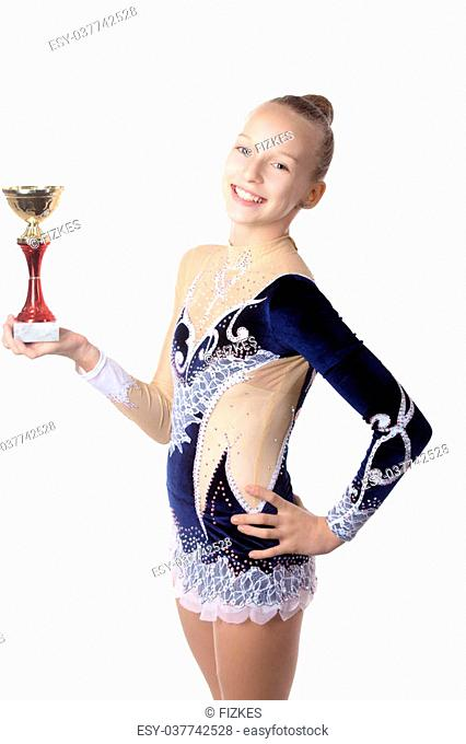 Portrait of beautiful happy smiling cool fit gymnast or skater young woman in sportswear dress posing with golden first place cup, studio, isolated