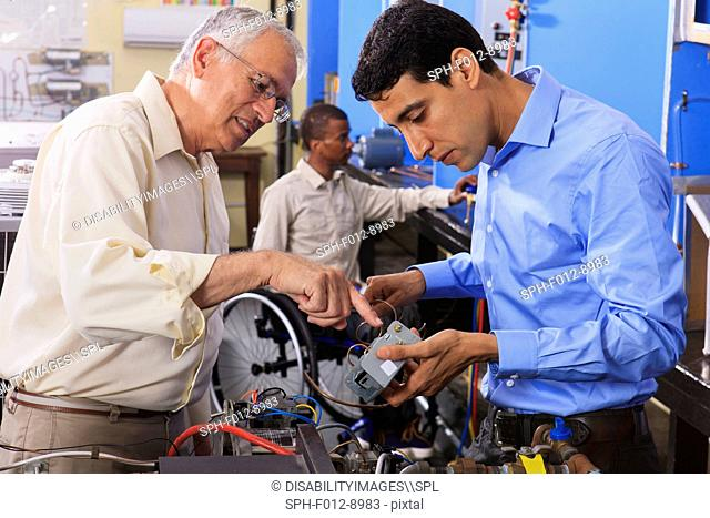 Student examining electrical control system on furnace with professor in HVAC classroom one student in wheelchair