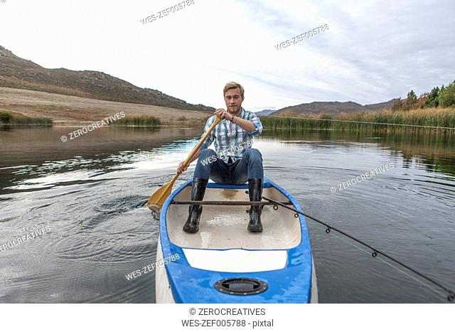 Portrait of young manwith fishing rod paddling on a lake