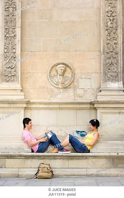 Couple on bench smiling at each other, side view
