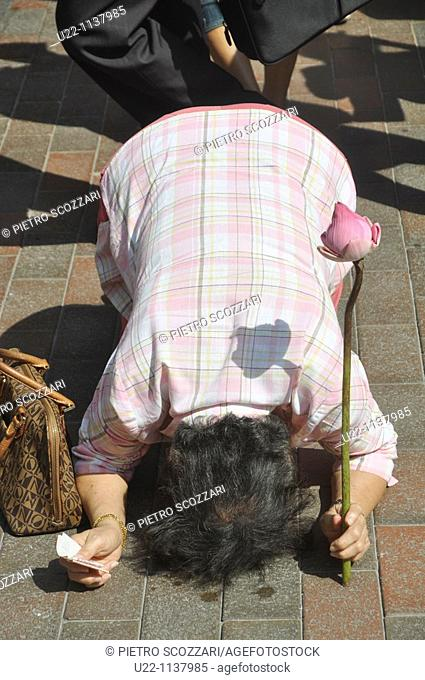 Singapore: a woman praying at the Goddess of Mercy Chinese Temple