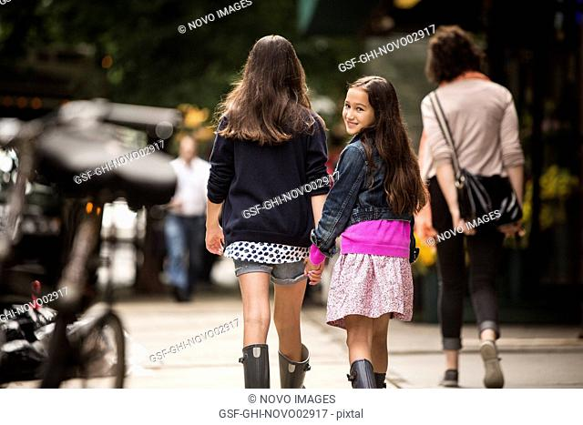 Two Young Girls Holding Hands While Walking Down Sidewalk, Younger Girl Looking Over Shoulder While Smiling, Rear View