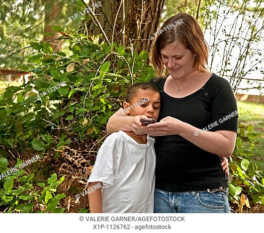 This young modern Caucasian mother is text messaging with her cute bi-racial son in a family moment together of learning technology Background is intentionally...