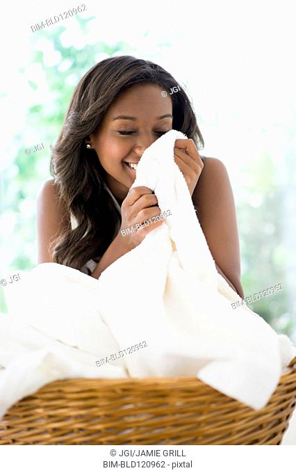 Black woman smelling clean towels