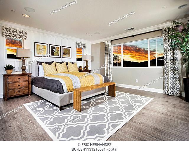 Spacious bedroom with view of sunset through window; Menifee; California; USA