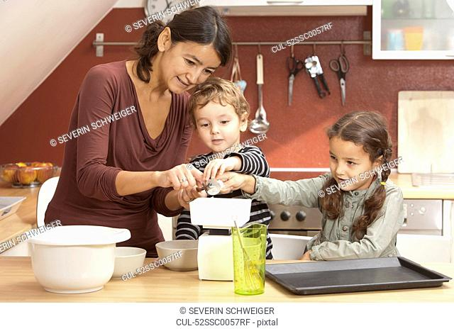 Mother and children cooking in kitchen
