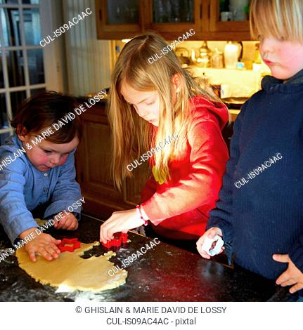 Brother and sisters making biscuits in kitchen