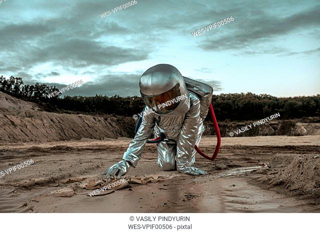 Spaceman exploring nameless planet, searching the soil