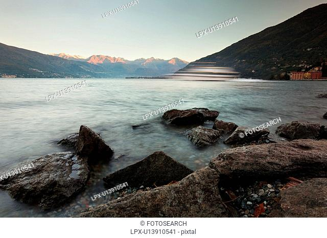 View of lake from rocky shoreline, wave and ferry boat motion slowed, pink light of sunrise on mountain range across Lake Como, Northern Italy