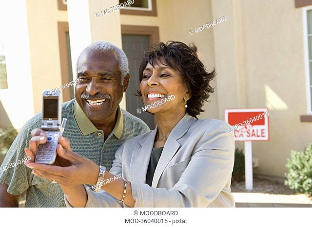Middle-aged couple photographing in front of new home