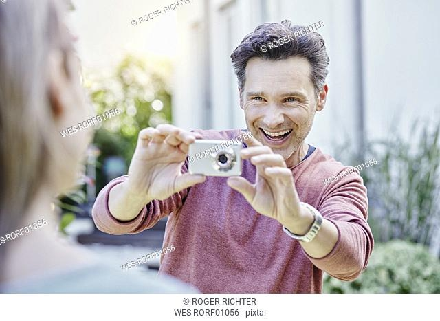Happy man taking picture of his wife outdoors